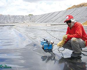 Profissional aplicando uma manta PEAD em uma vala escavada.