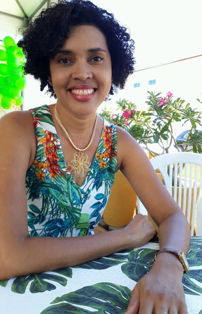 Prof. Dr. Débora de Gois Santos, usando um vestido florido em um dia ensolarado.